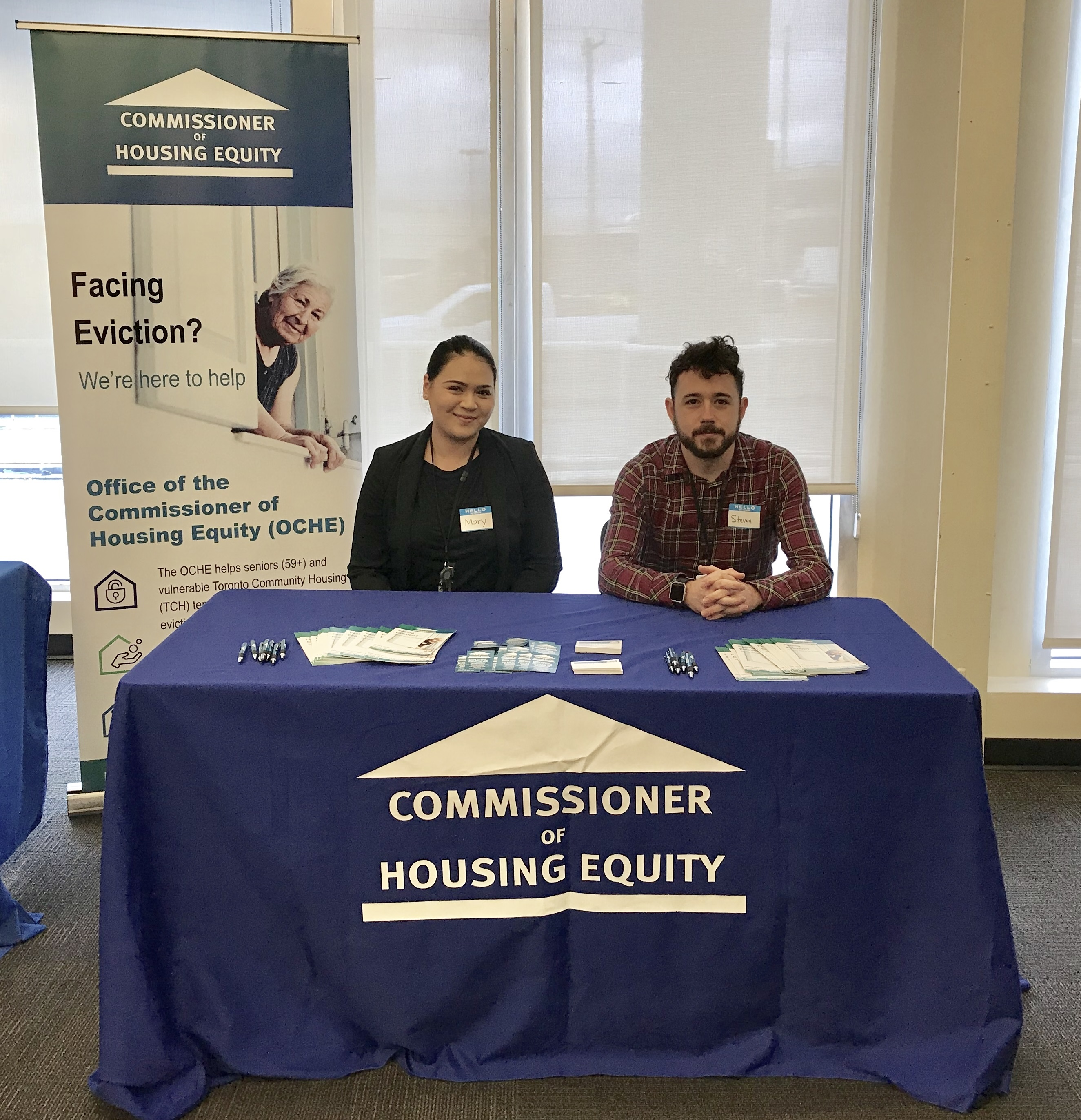 Two OCHE team members sitting at a table with brochures at Housing Information Fair
